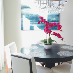 details of dining space with bright colored orchid center piece